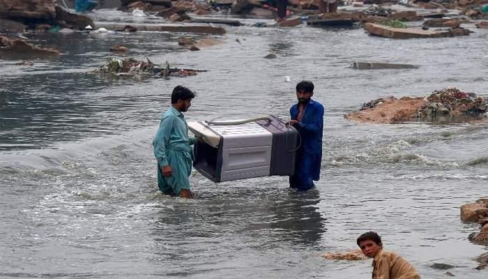 People carry a washing machine through flooded residential area after heavy monsoon rains in Karachi on August 27, 2020. — AFP/File