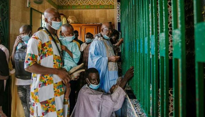Pilgrims cannot enter the mosque with a facemask. AFP