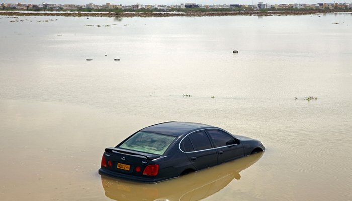 Vehicles make their way through a flooded street in the aftermath of tropical Cyclone Shaheen in Oman´s northern town of al-Mussanah on October 4, 2021. — AFP