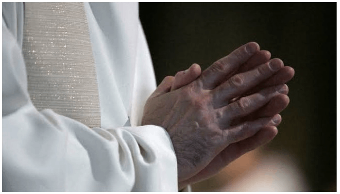 Hands of a member of a church raised for worship. Photo— AFP