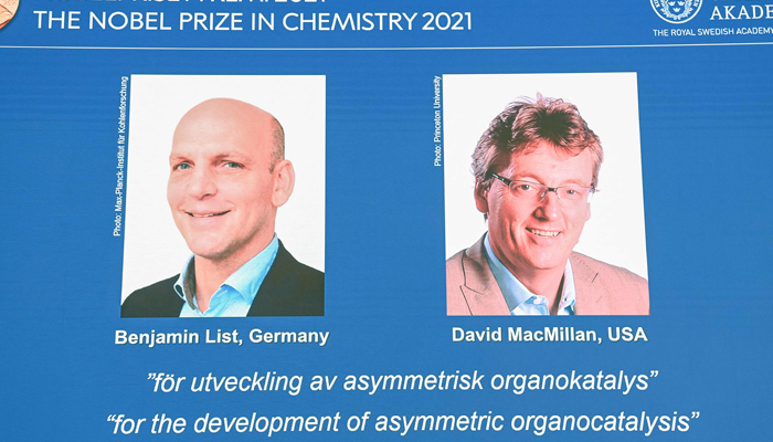 A screen displays the co-winners of the 2021 Nobel Prize in Chemistry, Germanys Benjamin List (L) and David MacMillan of the United States, during a press conference at the Royal Swedish Academy of Sciences in Stockholm, Sweden, on October 6, 2021. — AFP
